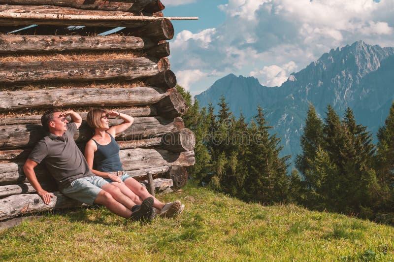 Junge Paare, die Ansicht von österreichischen Alpen genießen lizenzfreies stockfoto