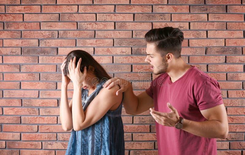 Junge Paare, die Argument nahe Backsteinmauer haben stockbild