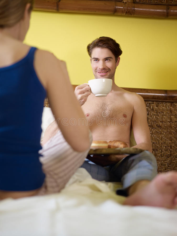 Junge Paare, die auf Bett frühstücken stockbild