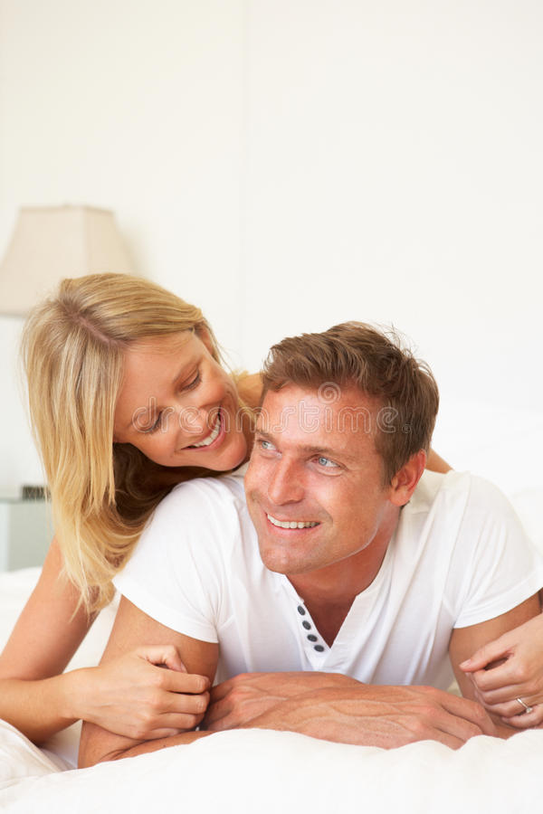 Junge Paare, die auf Bett sich entspannen lizenzfreies stockfoto