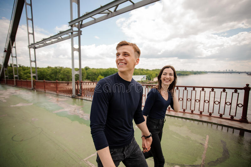 Junge Paare, die auf Brücke gehen lizenzfreies stockbild