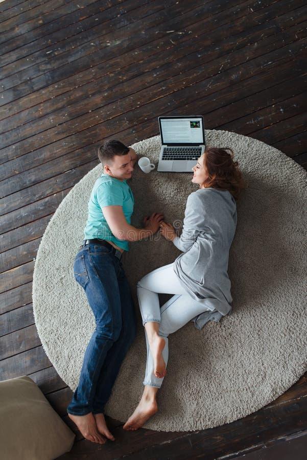 Junge Paare, die auf dem Boden mit Laptop liegen und miteinander sprechen stockbild