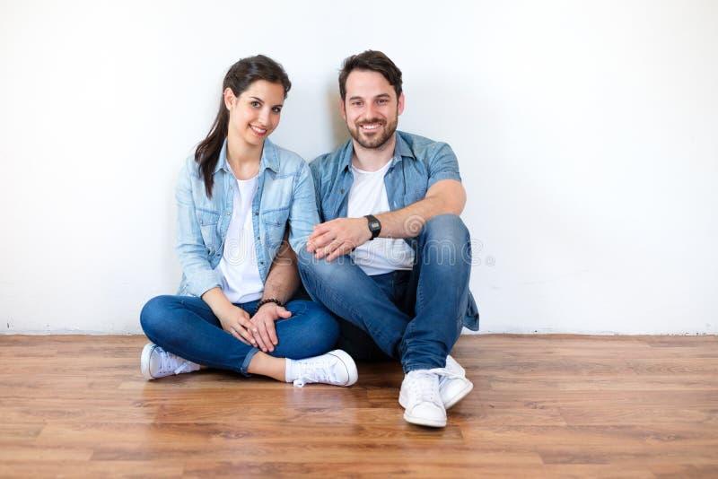 Junge Paare, die auf dem Boden projektiert ihr neues Haus und furn sitzen stockfoto