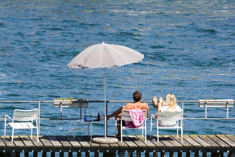 Junge Paare, die auf dem Flusspier sich entspannen stockfotos