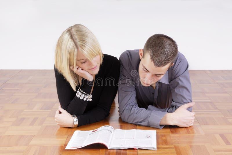 Junge Paare, die auf dem Fußboden liest eine Zeitschrift liegen stockfotografie