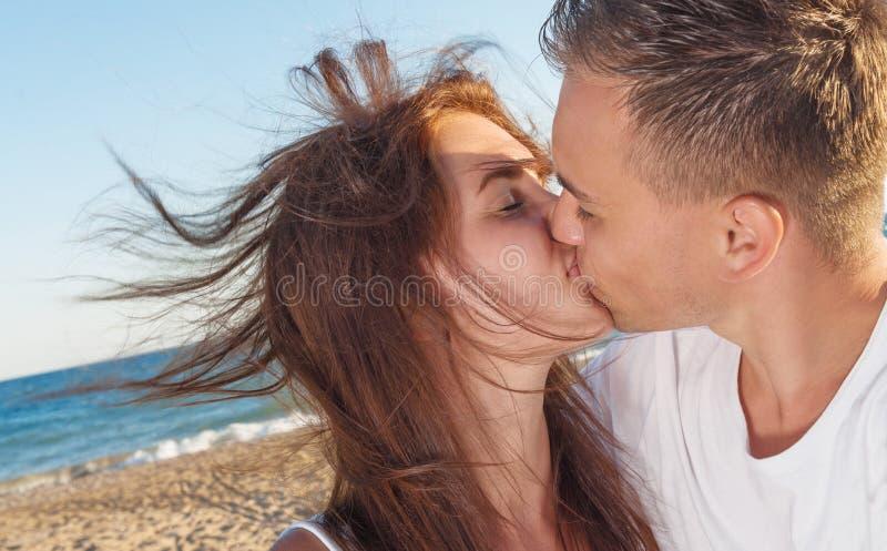 Junge Paare, die auf dem Strand küssen stockbild