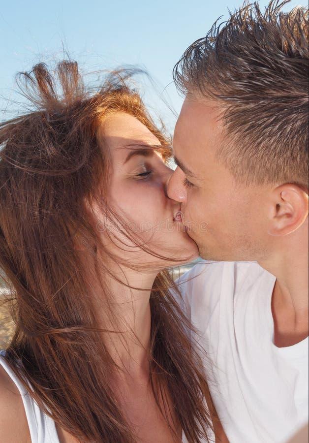 Junge Paare, die auf dem Strand küssen lizenzfreie stockbilder
