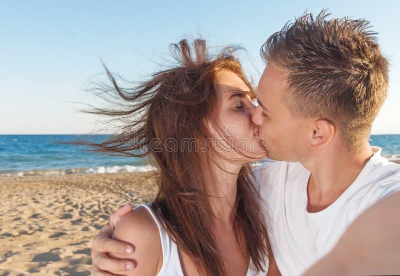 Junge Paare, die auf dem Strand küssen lizenzfreie stockfotografie