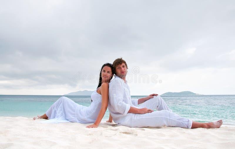 Junge Paare, die auf dem Strand nahe der Küste sitzen lizenzfreies stockfoto