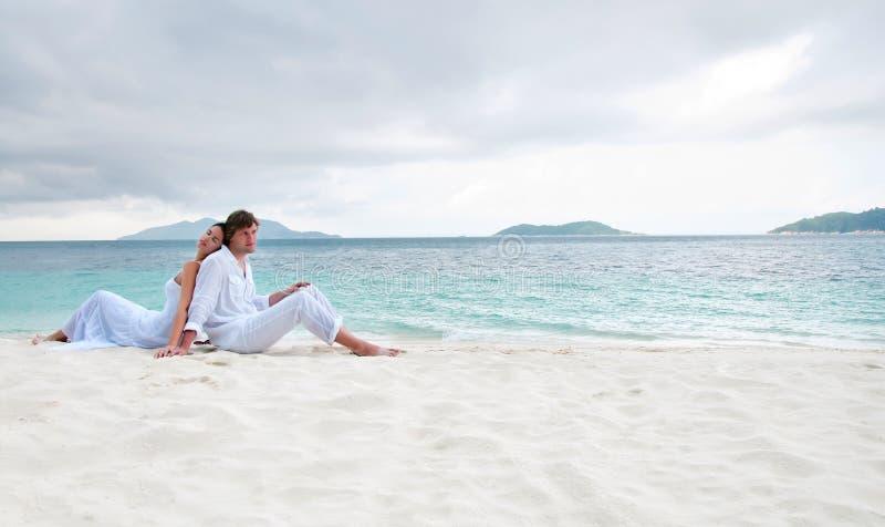 Junge Paare, die auf dem Strand nahe der Küste sitzen lizenzfreie stockfotos