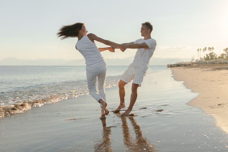 Junge Paare, die auf dem Strand spielen lizenzfreies stockbild