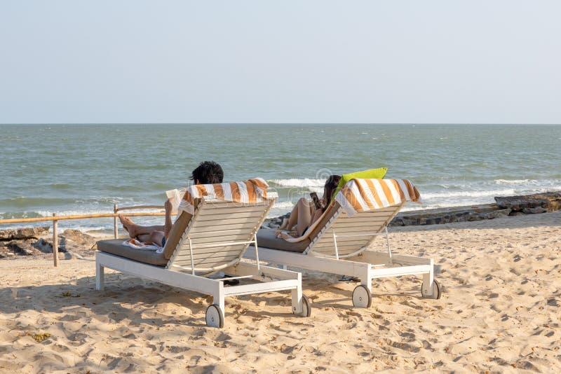 Junge Paare, die auf dem Strandstuhl-Lesebuch sich entspannen und Handy verwenden stockfotografie