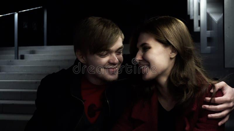 Junge Paare, die auf der Schrittunterhaltung sitzen Kaukasischer attraktiver Mann und Schönheit der liebevollen Paare, die auf St lizenzfreie stockfotos