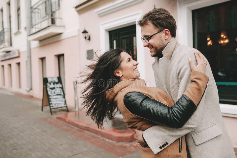 Junge Paare, die auf der Stadtstraße im Winter umarmen lizenzfreie stockfotos