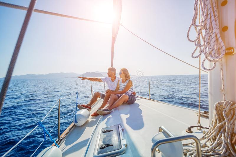 Junge Paare, die auf der Yacht sich entspannen stockfoto
