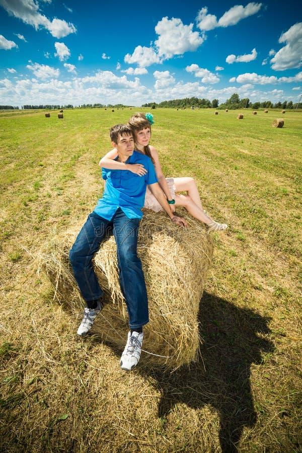 Junge Paare, die auf einem Heustapel sitzen stockbilder