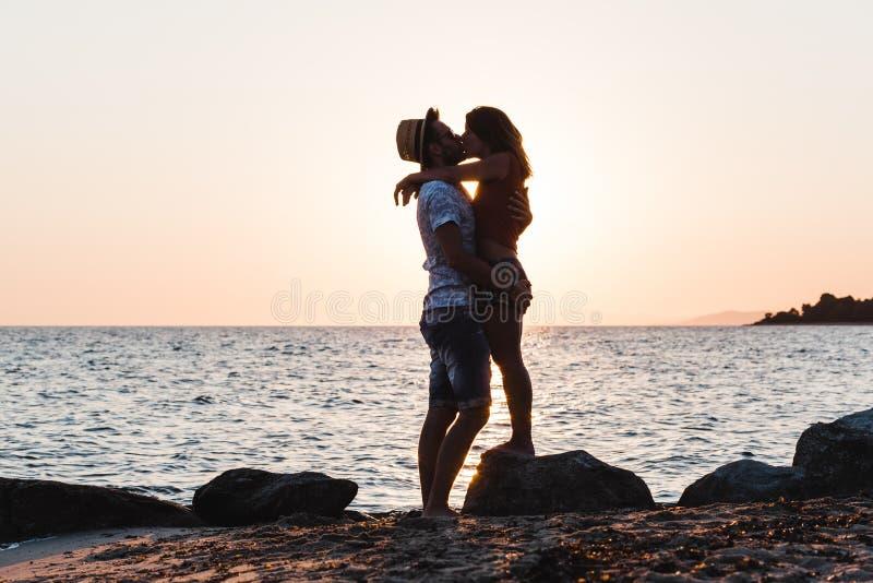 Junge Paare, die auf einem Strand umarmen und küssen stockbilder