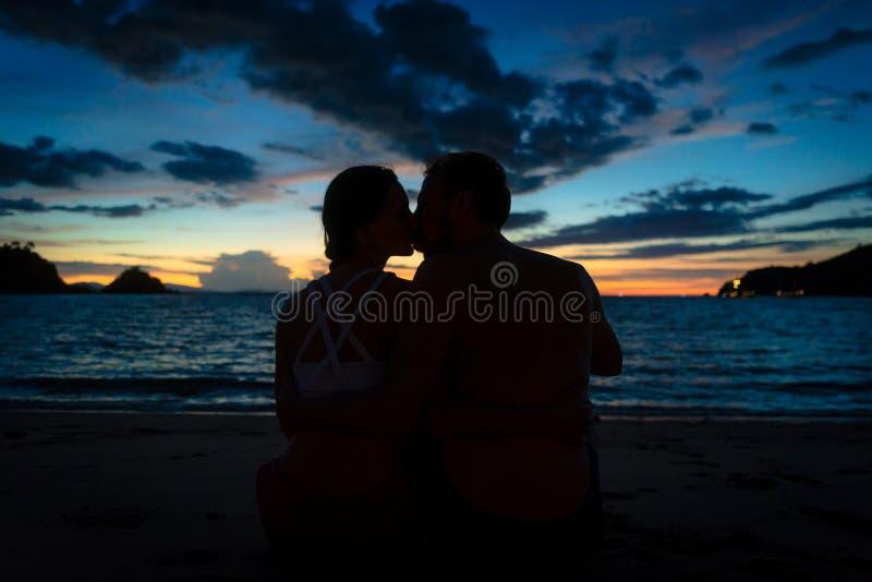 Junge Paare, die auf einem träumerischen Strand an der Dämmerung während der Sommerferien küssen lizenzfreie stockfotografie