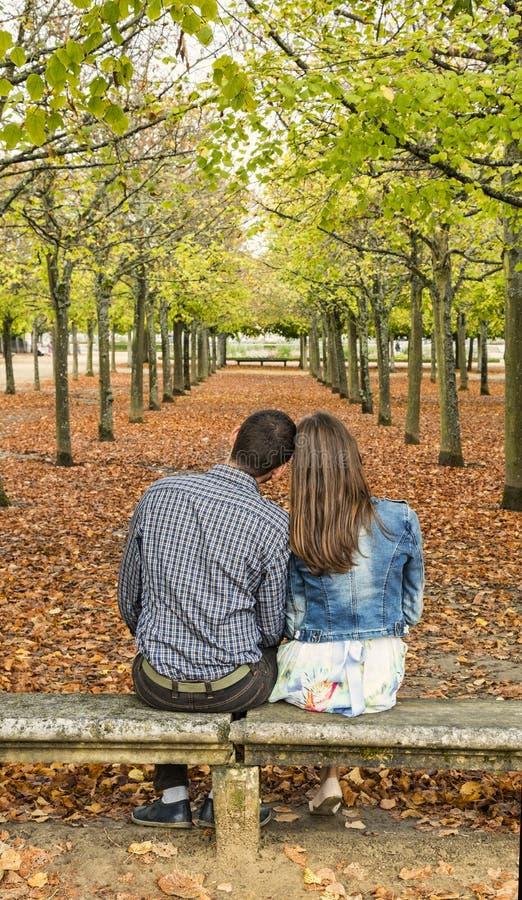 Junge Paare, die auf einer Bank in einem Park im Herbst sitzen stockbild