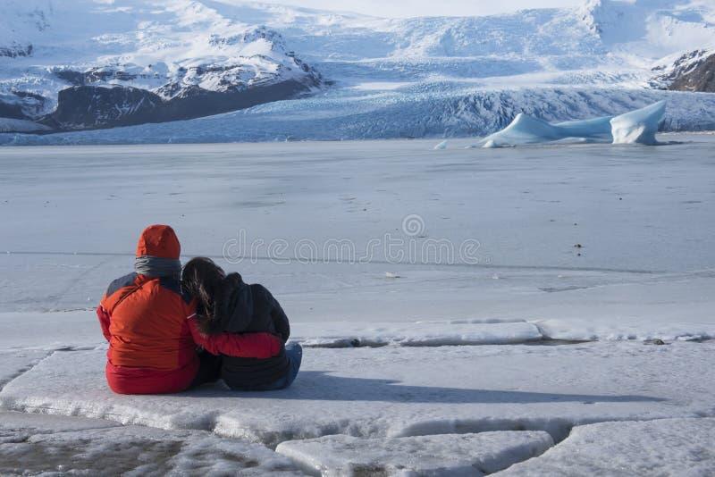 Junge Paare, die auf Eisberg sitzen und Jokulsarlon-glaci betrachten lizenzfreies stockbild