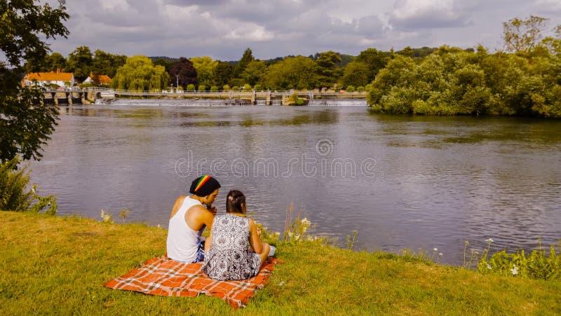 Junge Paare, die auf Flussbank sitzen stockfotos