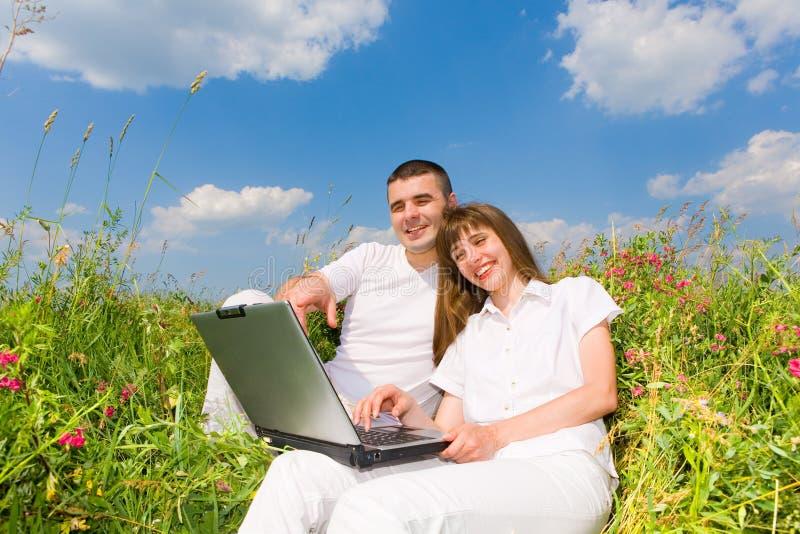 Junge Paare, die auf Grasfeld mit Laptop sitzen stockfotos