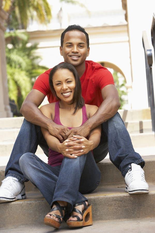 Junge Paare, die auf Jobstepps des Gebäudes sitzen lizenzfreies stockbild