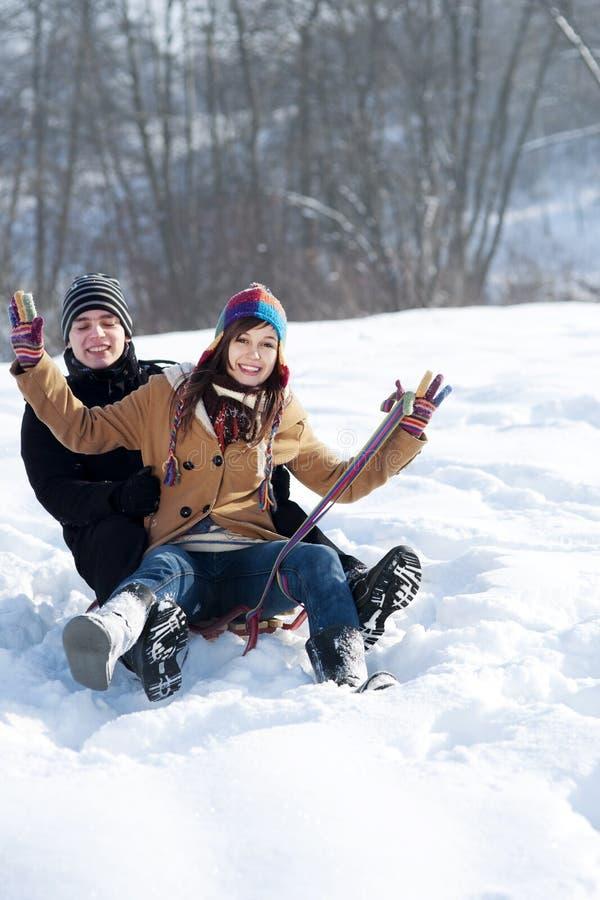 Junge Paare, die auf Schnee sledding sind stockfoto