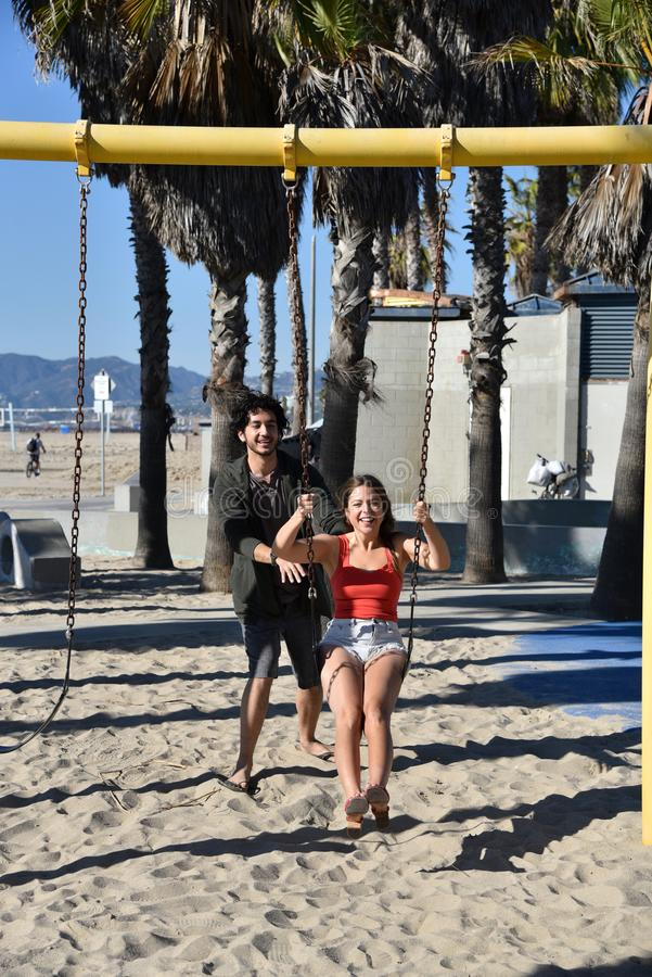 Junge Paare, die auf Schwingen am Strand spielen lizenzfreies stockbild