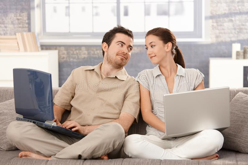 Junge Paare, die auf Sofa unter Verwendung des Laptoplächelns sitzen lizenzfreies stockfoto