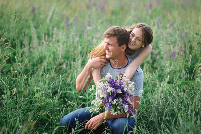 Junge Paare, die auf Sommerwiese umfassen stockfotografie