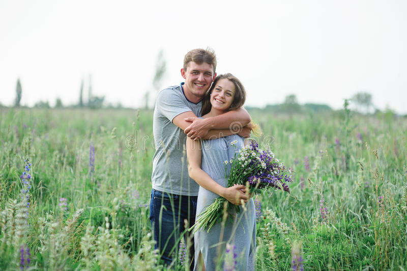 Junge Paare, die auf Sommerwiese umfassen lizenzfreies stockfoto