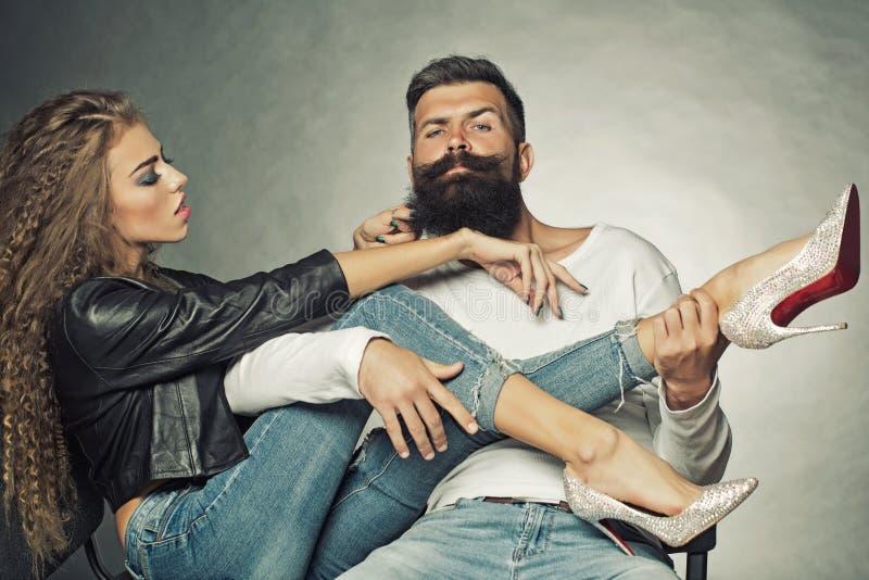 Junge Paare, die auf Stühlen sitzen stockbild