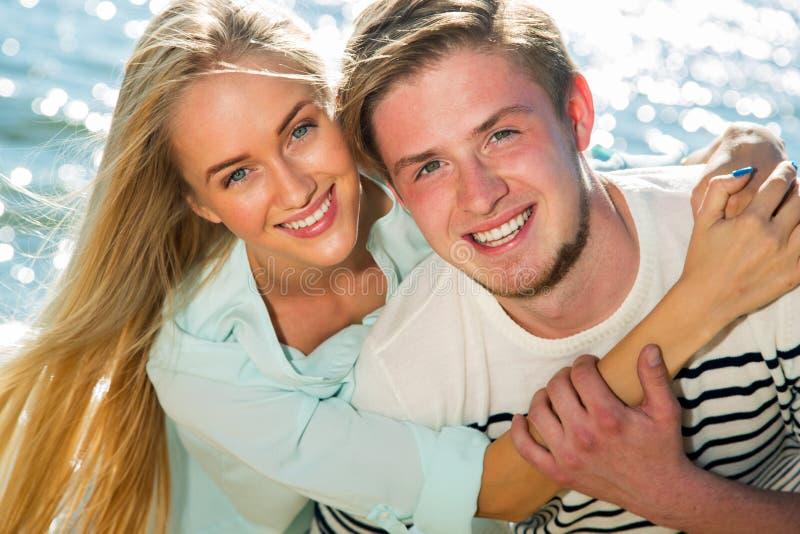 Junge Paare, die auf Strand gehen lizenzfreie stockfotos