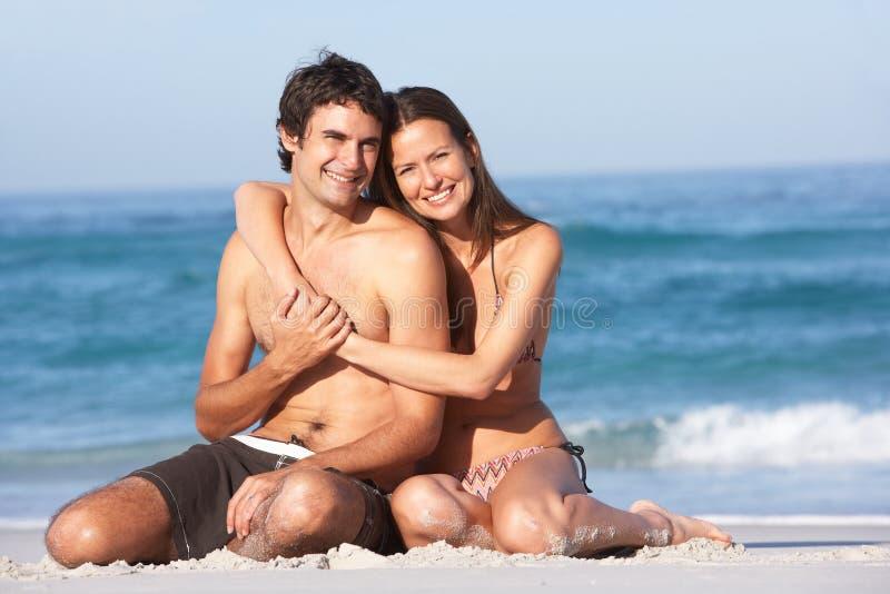 Junge Paare, die auf Strand-tragender Badebekleidung sich entspannen