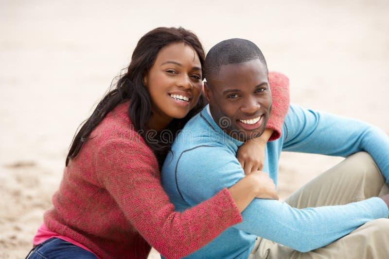 Junge Paare, die auf Strand umfassen stockfotos