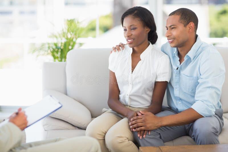 Junge Paare, die auf Verkäufer auf der Couch hören lizenzfreie stockbilder