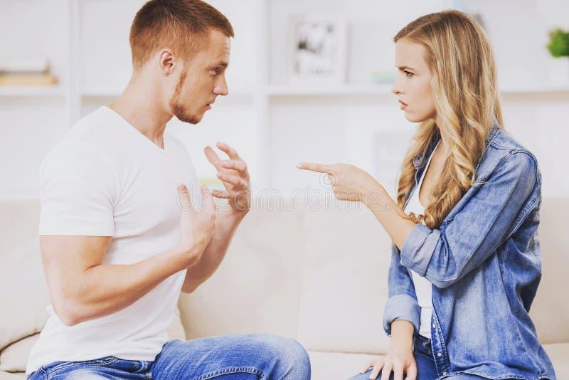 Junge Paare, die auf weicher Couch am süßen Haus argumentieren lizenzfreie stockbilder