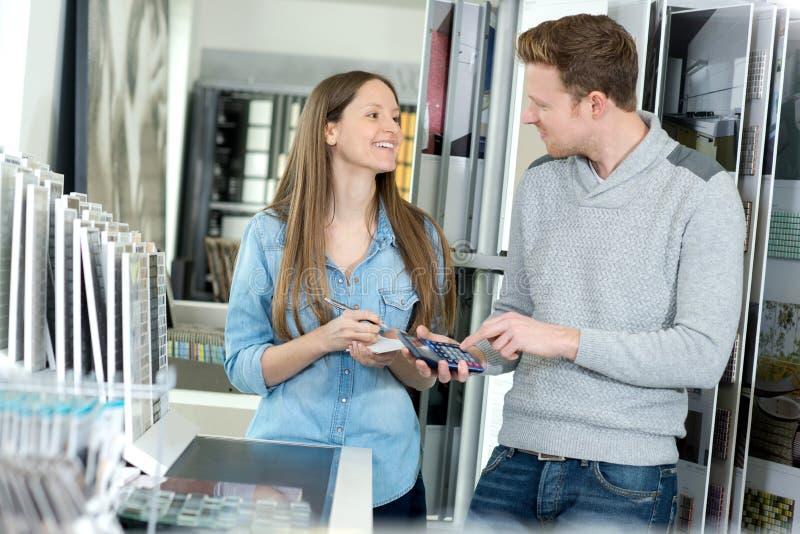 Junge Paare, die Badezimmerhähne wählen, wenn Speicher plombiert wird lizenzfreie stockfotografie