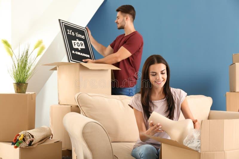 Junge Paare, die bewegliche Kästen am neuen Haus auspacken stockbild