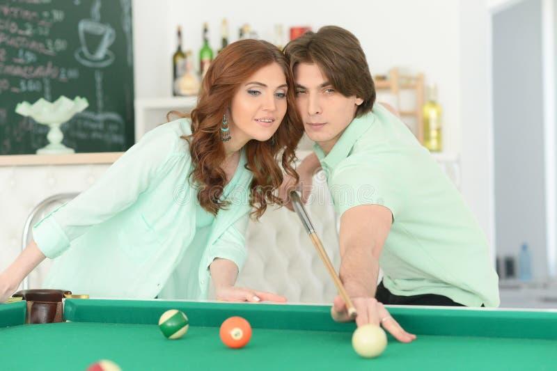 Junge Paare, die Billard spielen lizenzfreies stockfoto