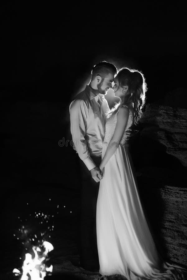 Junge Paare die Braut und der Bräutigam warm um das Feuer stockfoto