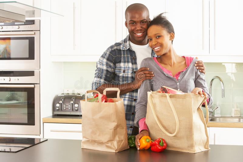 Junge Paare, die das Einkaufen in der modernen Küche entpacken lizenzfreie stockfotografie
