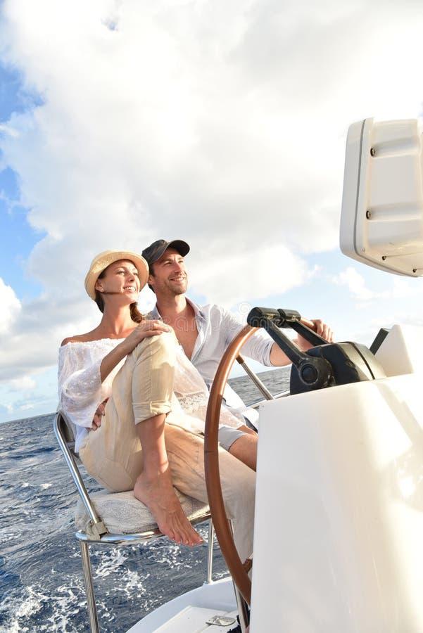Junge Paare, die das Segelboot leitend genießen stockfotografie