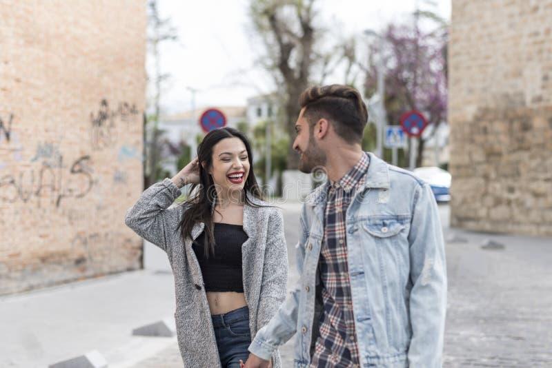 Junge Paare, die in das Straßenlächeln und -c$lachen gehen stockfoto