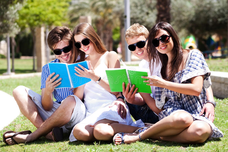 Junge Paare, die in den Park- und Lesebüchern sich entspannen lizenzfreie stockfotos