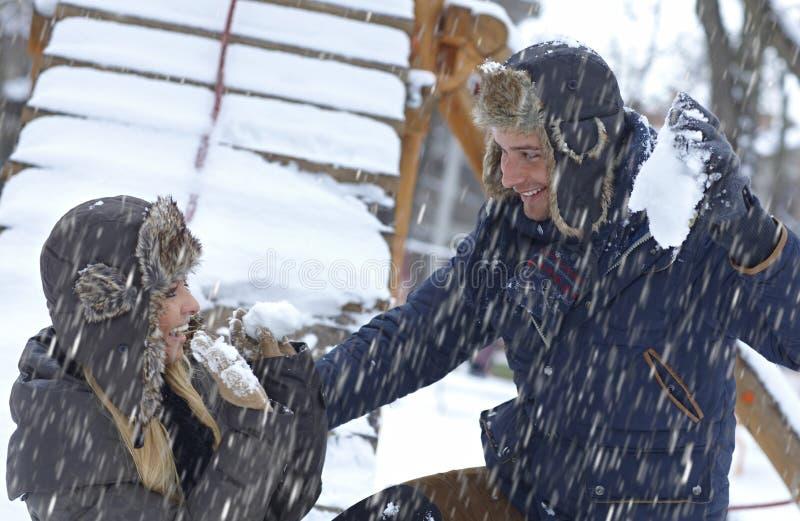 Junge Paare, die in den Schneefällen spielen lizenzfreies stockbild