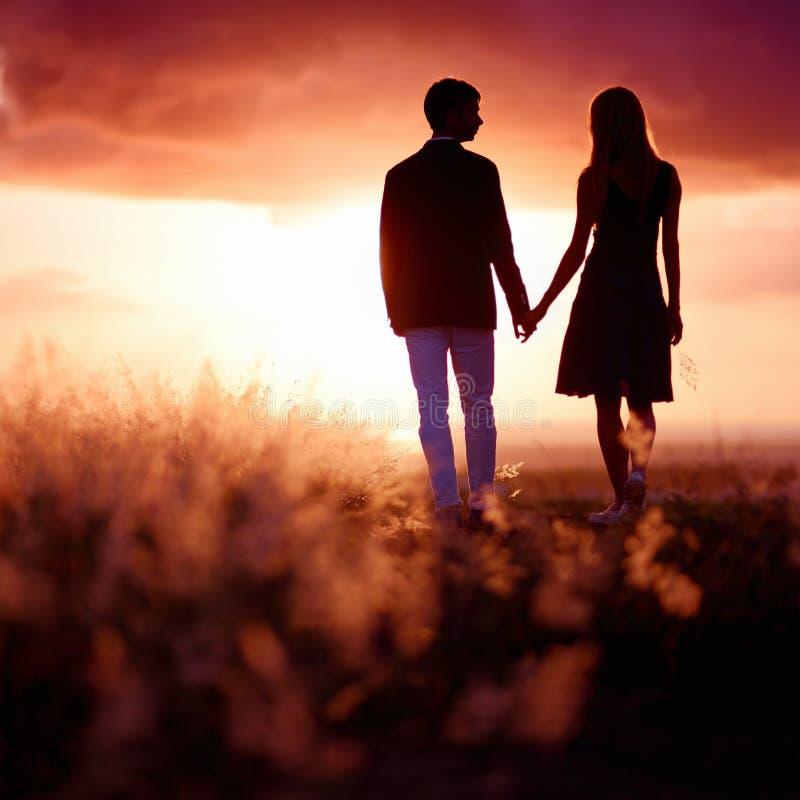 Junge Paare, die den Sonnenuntergang genießen lizenzfreies stockbild