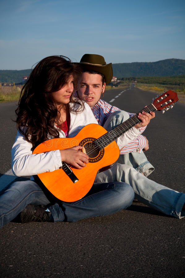 Junge Paare, die in der Mitte der Straße mit Gitarre sitzen stockbilder