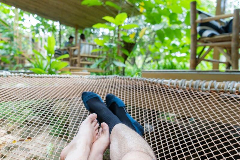 Junge Paare, die in der Nettohängematte im Wald sich entspannen stockfotos